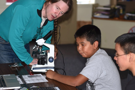 Researcher demonstrating a microscope to young rural community student