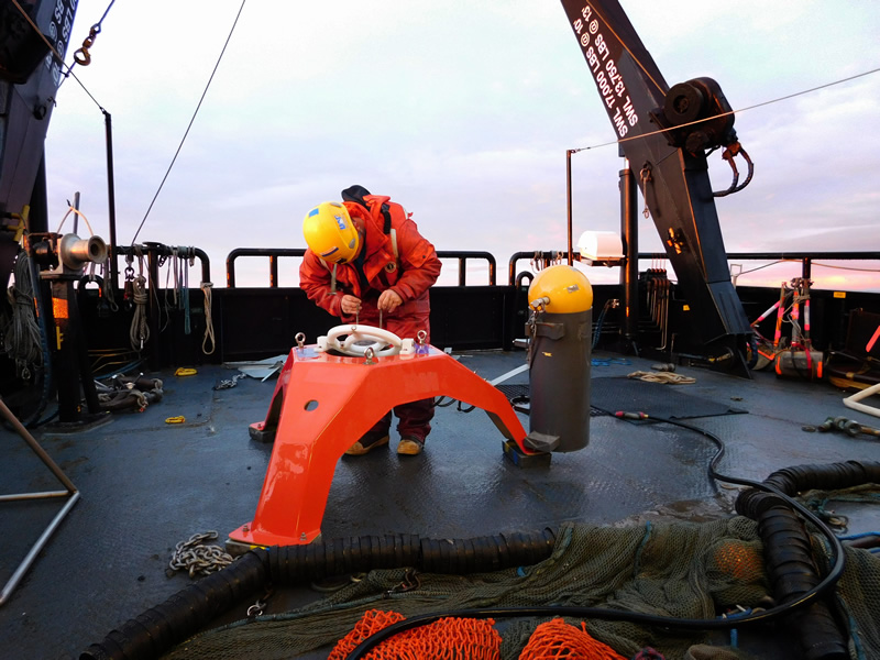 lone researcher working on the back deck of a vessel attaching sensors to a mooring